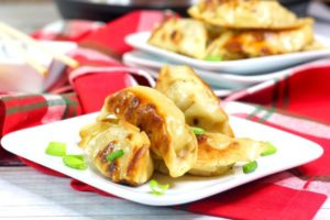 A plate of pot stickers with golden brown edges and topped with sliced green onions.
