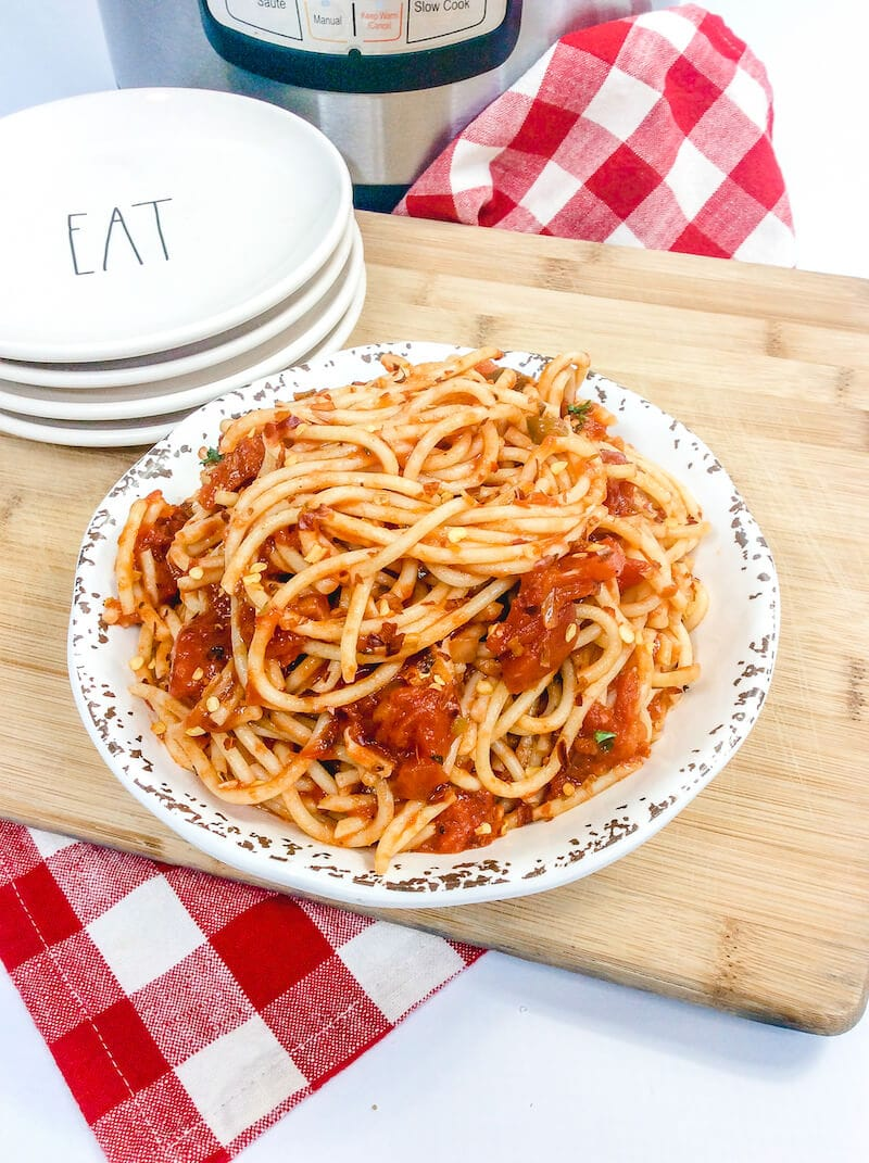 A white plate piled high with spicy spaghetti over a checkered tablecloth with an instant pot in the background.