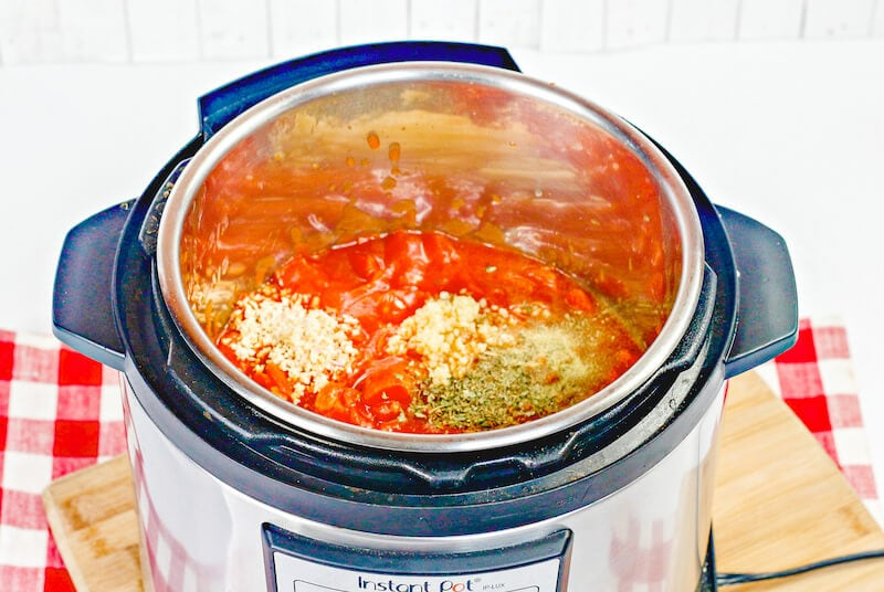 Instant pot filled with spicy spaghetti ingredients.