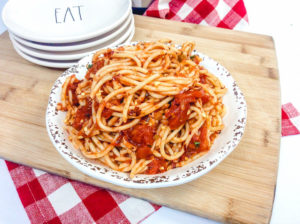A cutting board with a plate piled high with spaghetti.