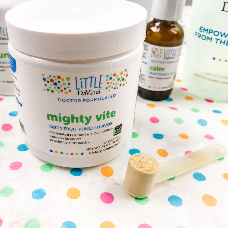 A scoop of Mighty Vite next to jar of Mighty Vite.