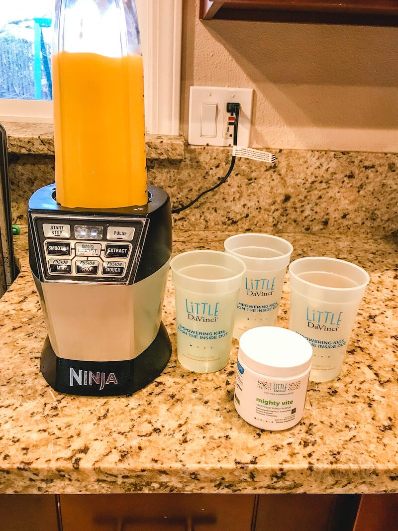An orange smoothie in a blender next to three plastic cups and jar of Mighty Vite.