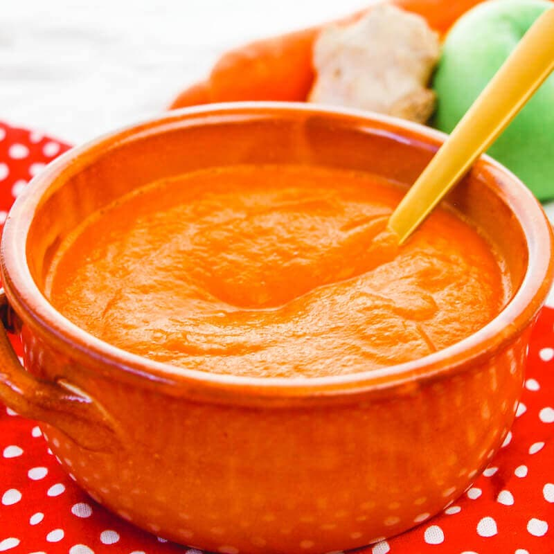A stoneware bowl filled with carrot soup.