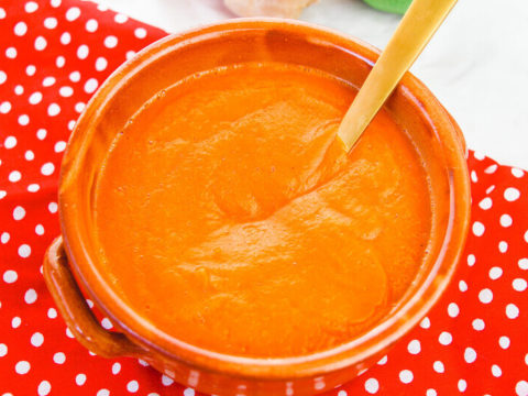 Overhead shot of roasted carrot soup on top of a red polka dot place mat.
