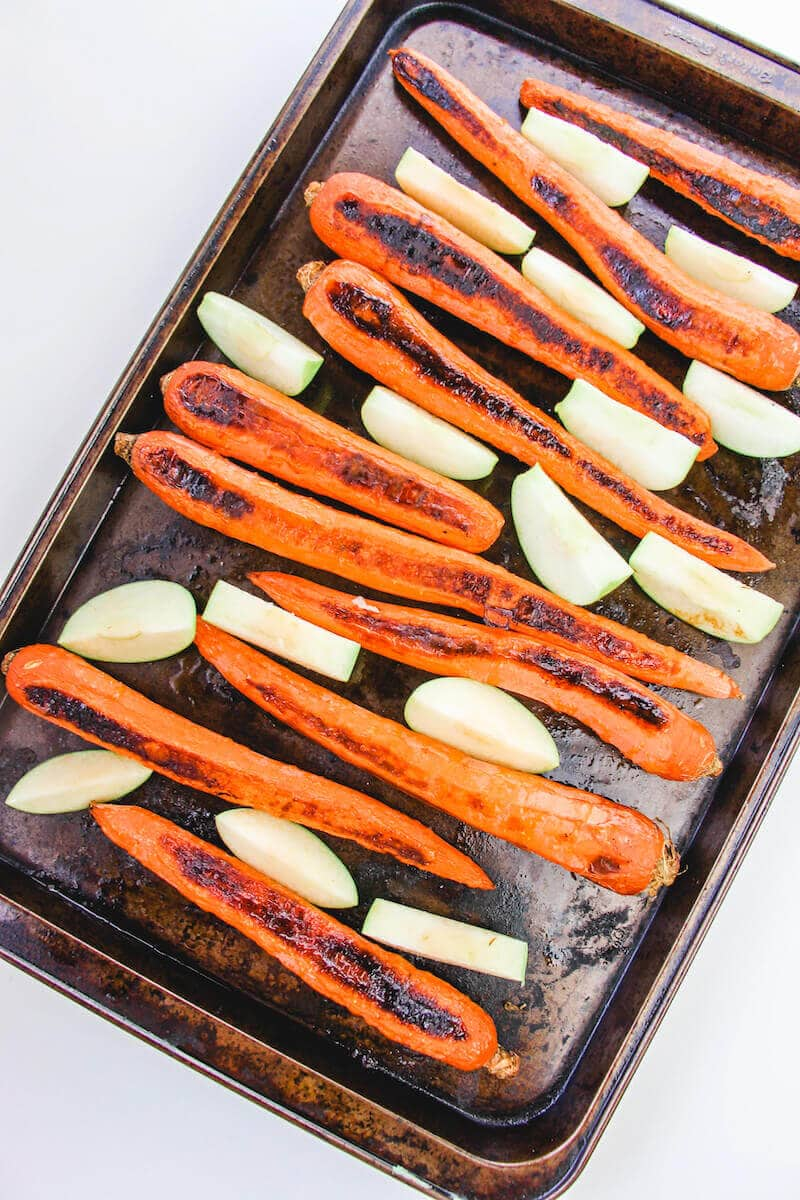 Carrots and apples on a cookie sheet.
