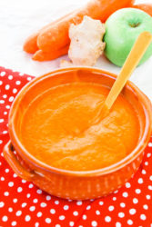 A bowl of carrot soup with carrots, apples, and ginger in the background.