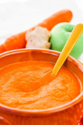 A bowl of carrot soup with a gold spoon sticking out of the bowl.