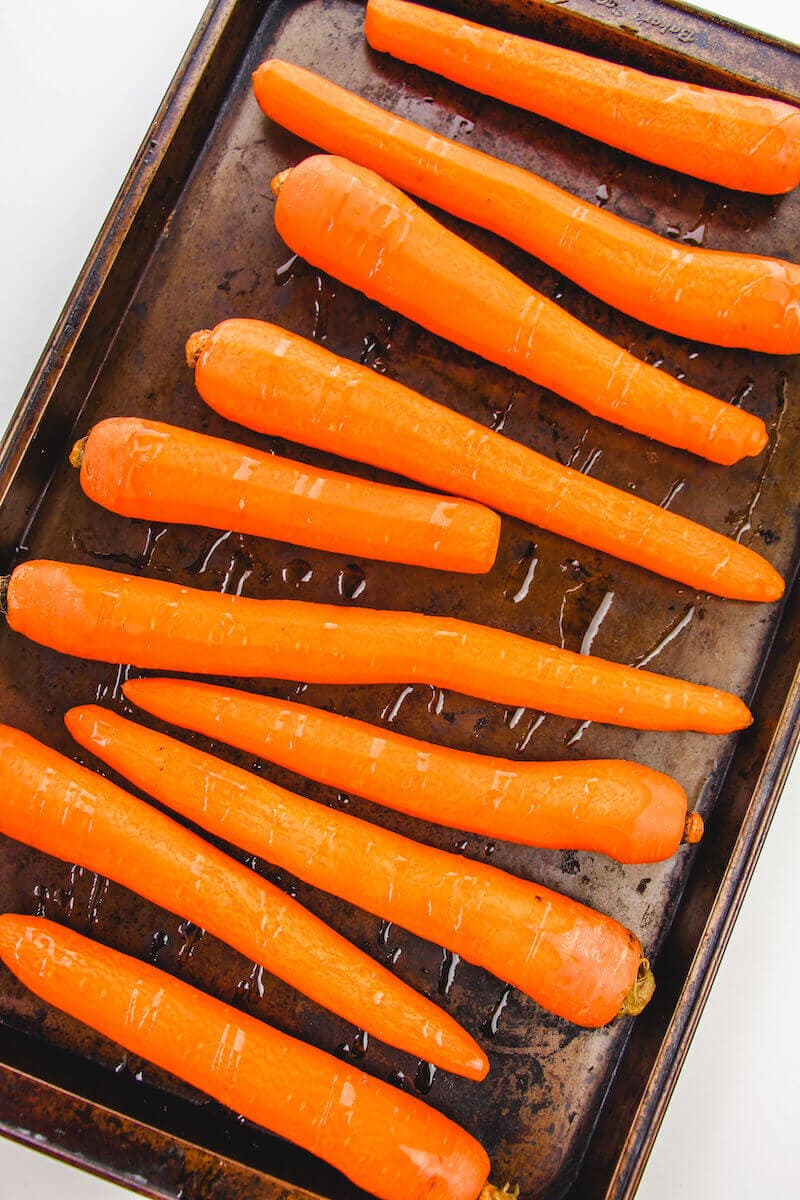 Peeled carrots on a cookie sheet and drizzled with oil.