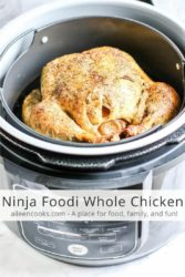 "A whole chicken with crispy skin inside a Ninja Food with the words ""Ninja Foodi Whole Chicken"" in black letters."