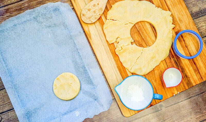 Shortbread cookie dough cut into a circle and on a cookie sheet.