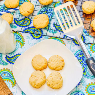 A blue and green place mat with a white plate of shortbread cookies, bottle of milk, and metal spatula on top.