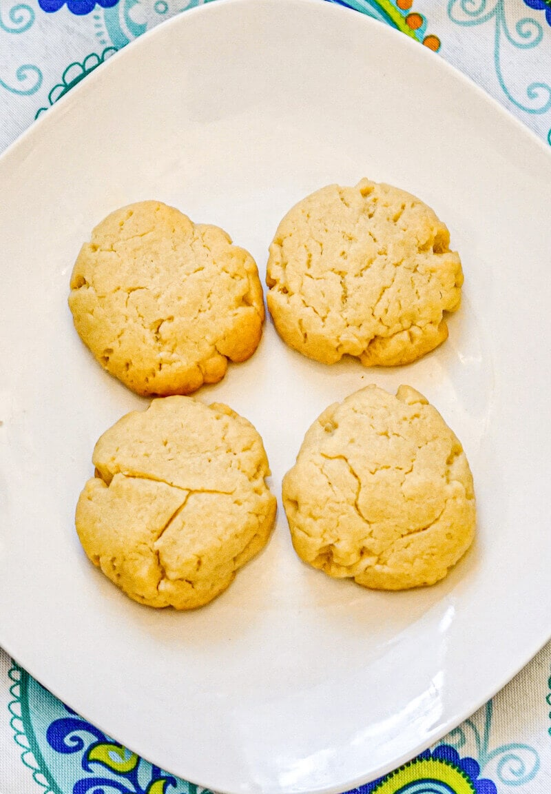 Close up of 4 shortbread cookies on a white plate.