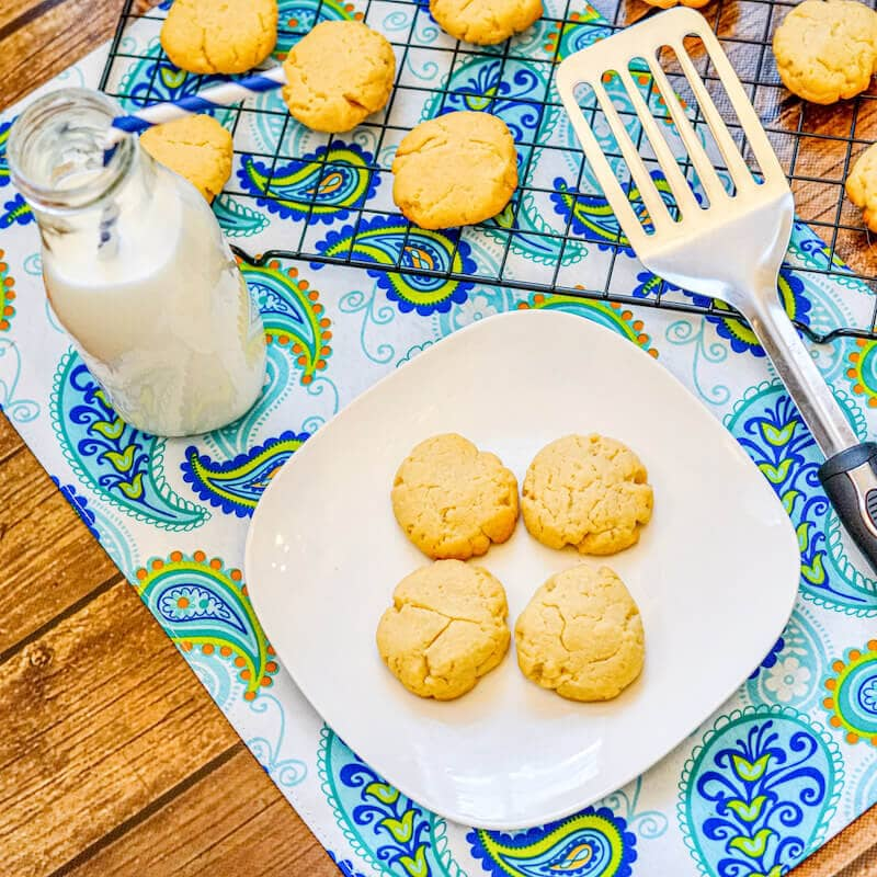 A glass bottle of milk next to a white plate with four shortbread cookies on it.