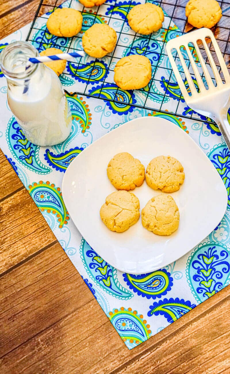Overhead shot of a plate of cookies next to a cooling rack full of 3 ingredient shortbread cookies.