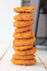 A stack of fried pickles on a white counter.