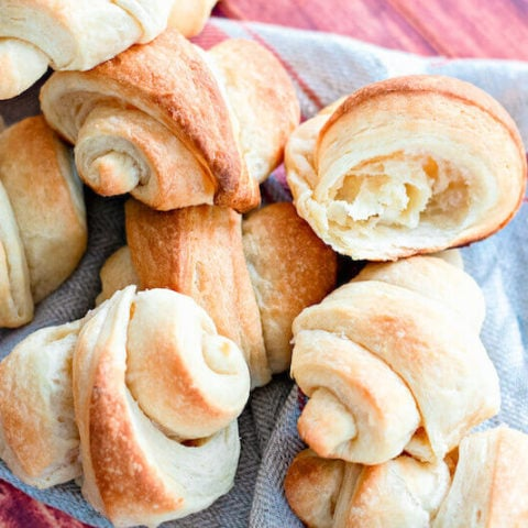 A pile of freshly baked crescent rolls on a blue tea towel.