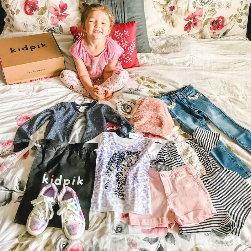 A little girl sitting on a bed with the clothes from her KidPik box laid out in front of her.