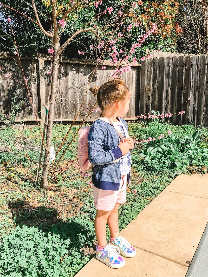 A little girl in light pink shorts and blue jacket looking over her shoulder, away from the camera.
