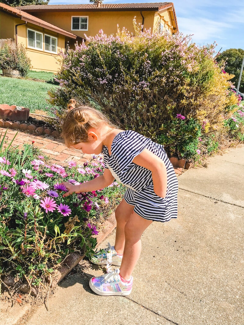 A girl in a black and white striped romper bending over to smell purple flowers on a bush.