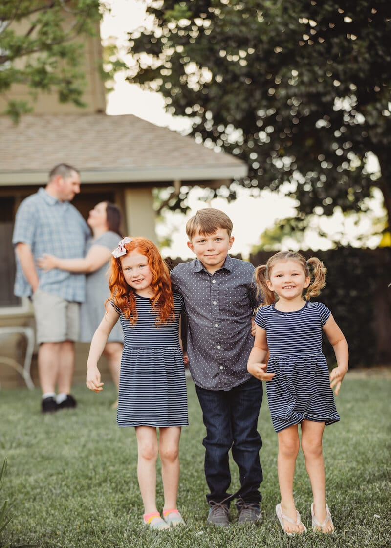 Three kids standing next to each other with their parents hugging in the background.