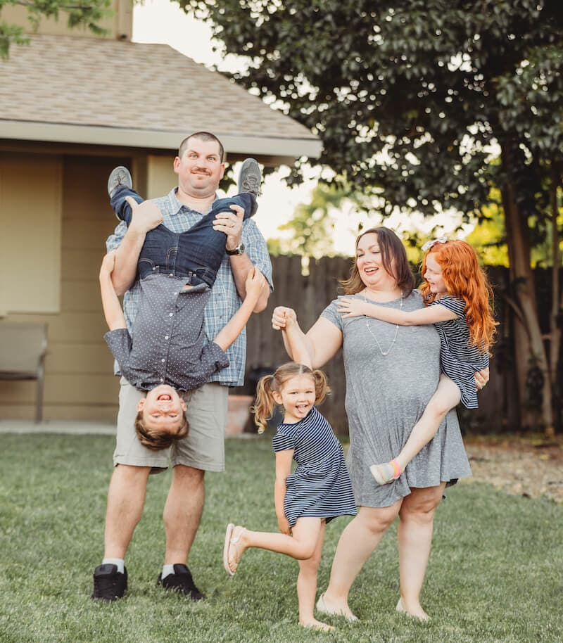 A family standing together with little boy held upside down by dad, one girl held by mom while other girl twirling on her mom's finger.
