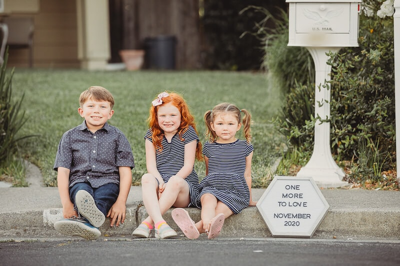 "Three kids sitting on a curb next to a letter board that says ""one more to love November 2020"""