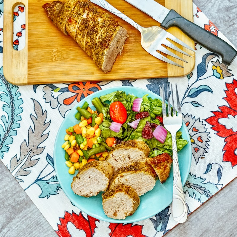 A blue plate loaded with sliced pork tenderloin and cooked vegetables next to a cutting board with pork tenderloin on a steak knife.
