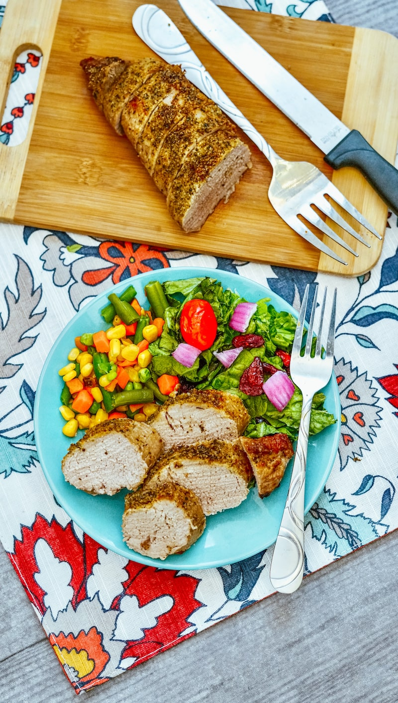 A floral tablecloth with a plate of pork tenderloin with mixed veggies next to a cutting board with a pork tenderloin cut in half.