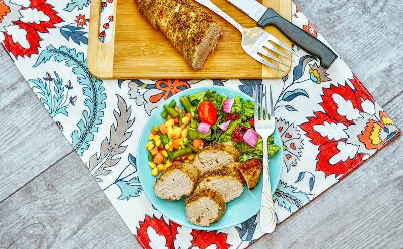 A floral placemat with a cutting board topped with pork tenderloin and a light blue plate of pork and vegetables.