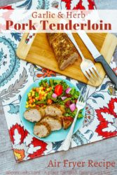 """A plate of pork tenderloin over a floral placemat with the words """"garlic & herb pork tenderloin"""" in red lettering."""