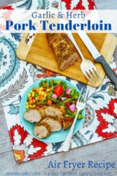 """A plate of pork tenderloin over a floral placemat with the words """"garlic & herb pork tenderloin"""" in blue lettering."""