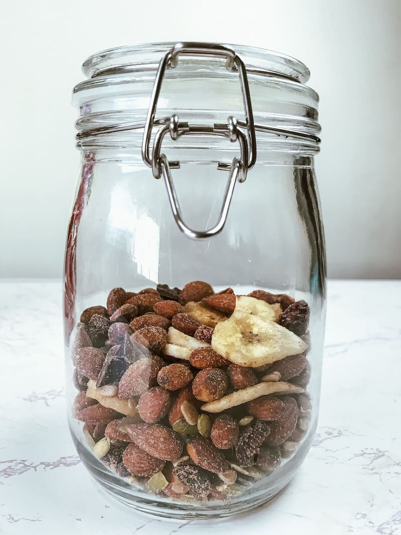 A glass jar with metal clamp, filled half-way with spicy trail mix.