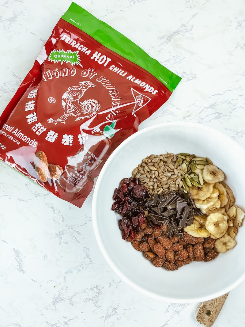 A large red bag of Sriracha hot chili almonds next to a white ceramic bowl filled with trail mix ingredients.