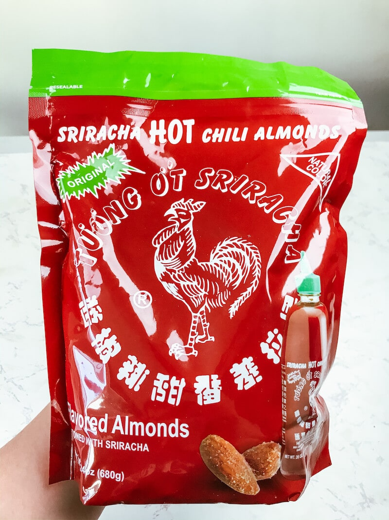 A hand holding up a large bag of Sriracha Almonds.