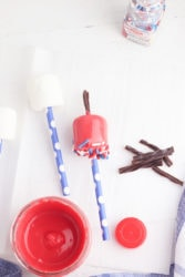 A plain marshmallow on a straw next to a red dipped marshmallow with black licorice sticking out the top and red, white, and blue sprinkles on the bottom.