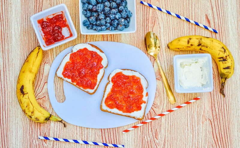 A white plate with two slices of toast topped with cream cheese and strawberry jam.