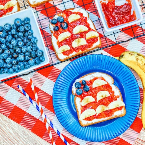 A piece of toast decoarated to look like an American flag next to a banana, bowl of blueberries, and bowl of strawberry jam.