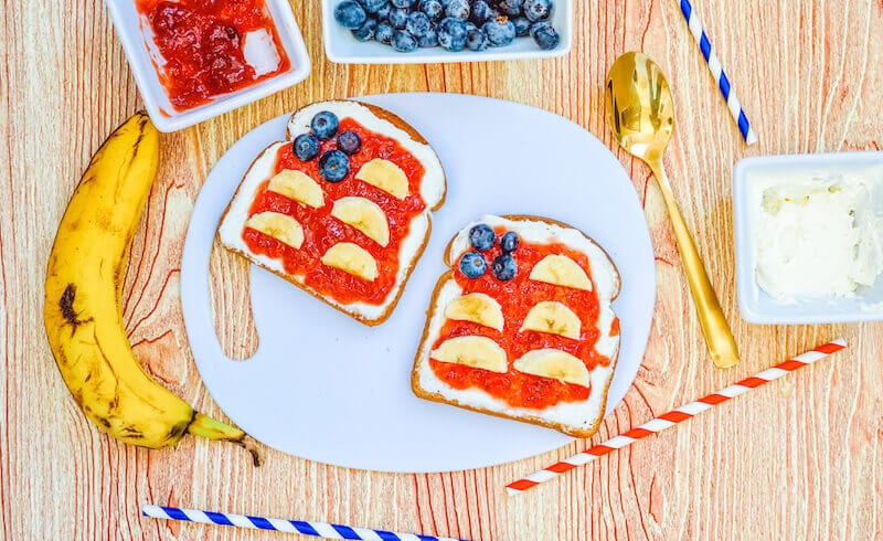 A white plate with two pieces of toast decorated to for an American flag using strawberry jelly, banana, and blueberries.