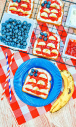 A red and white checkered placemat topped with a blue plate holding a piece of toast decorated to look like an American Flag.