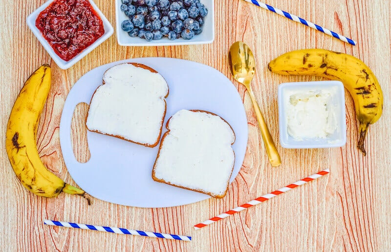 A white plate with two pieces of toast with cream cheese spread on them.