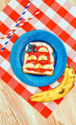 Toast decorated to look like an American Flag on a blue plate next to a banana.