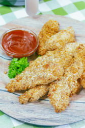 Air fried chicken strips on a green and white gingham tablelcloth.