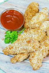 Close up of chicken tenders on a wooden plate.