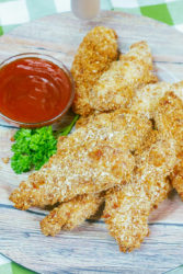 Chicken strips coated in pretzel crust on a wooden plate.