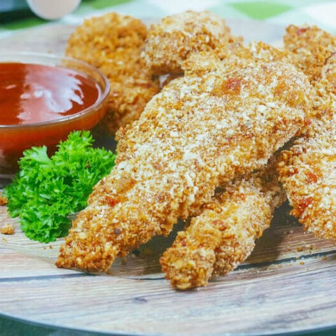 Side view of a plate of air fried chicken strips next to a small dish of ketchup.