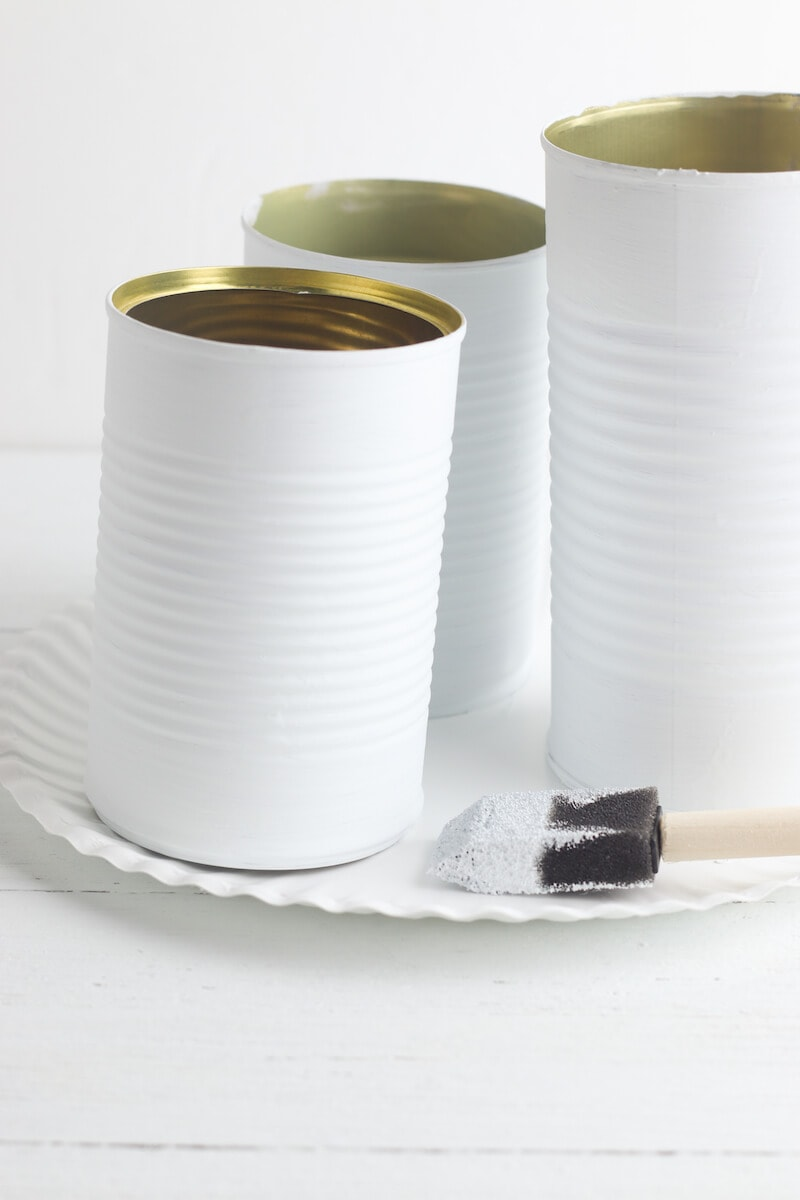 Three tin cans painted white.