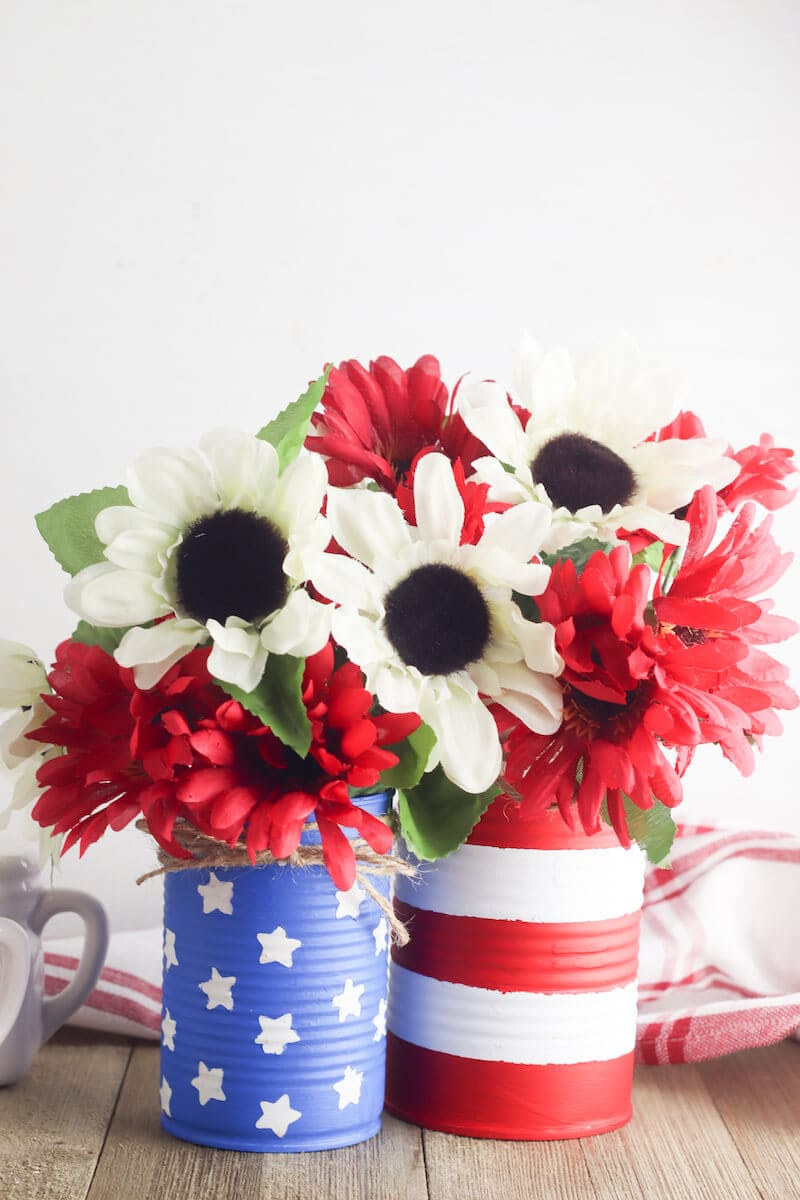 Two diy vases painted to look like the American flag and filled with white and red flowers.
