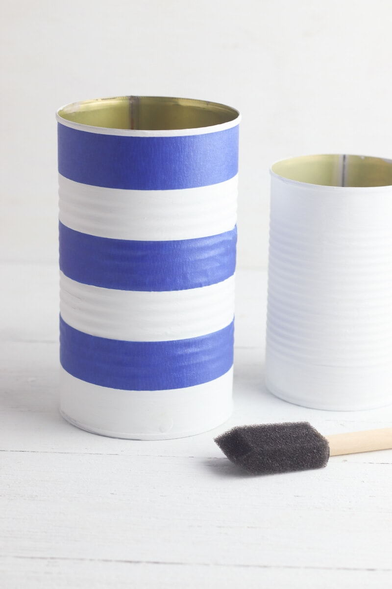 One of the cans with blue painters tape attached to make stripes.