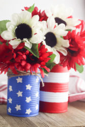 Two diy vases, one blue with white stars and one with red and white stripes, filled with flowers.