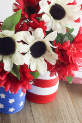 Close up of white flowers inside american flag painted vases.
